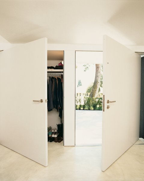 Oversize doors in the front entry create the sense of continuous wall when closed.