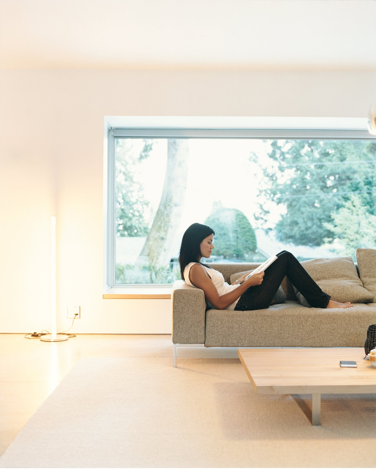 Griffith lounges on a Zanotta sofa in the sparely furnished living room. On the Level - Photo 5 of 13