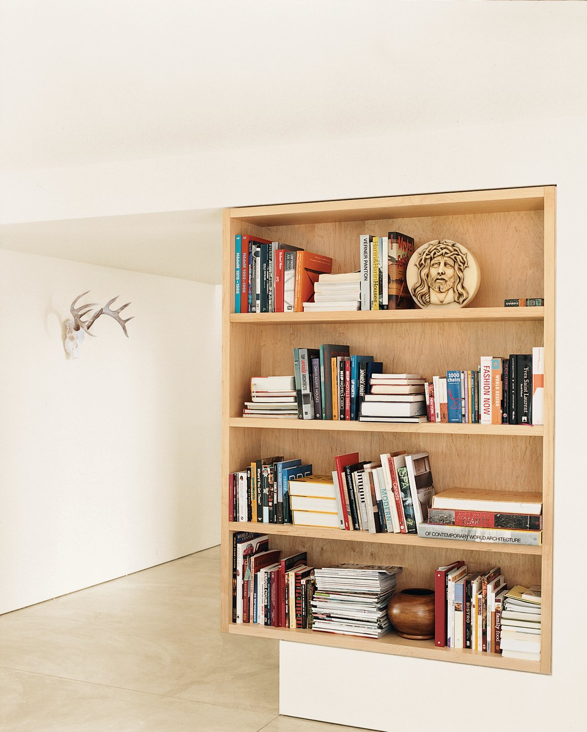 A maple bookcase defines the point between the living room and foyer.  Photo 12 of 13 in On the Level