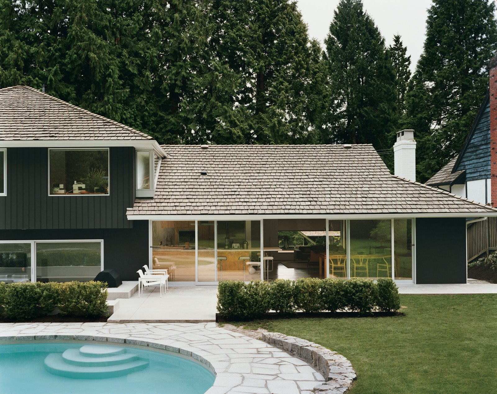 After trying dozens of colors, LeBlanc says, they settled on basic black for the exterior as   a way to best marry the building with its forest surroundings, which include 30-foot-high western red cedar trees. The pool is original; but the deck, once made of concrete, has been reclad in granite to match the old retaining wall.