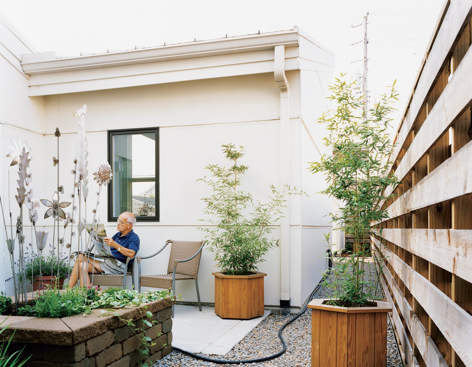 """The Brachers spend large amounts of time lounging in their courtyard spaces, as Peter demonstrates. """"Whatever room you're in on the first floor, you're looking at some type of garden. That was the whole idea of the project,"""" the architect explains.  Photo 4 of 4 in Suburban Flight"""
