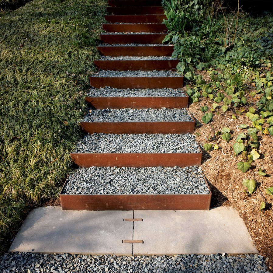 The stairs going up the knoll to the roof garden and to the house's second-level entrance are made from Cor-Ten steel risers (which develop a rich, rusted patina) and filled with gravel in order to create a nonslip surface that drains well. Steel and steelwork by Virginia Industrial.  190+ Best Modern Staircase Ideas by Dwell from This House Tells the Time With an Oculus