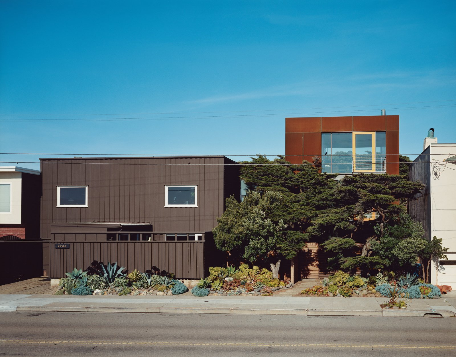 Born's original house (far left) only gave two glimpses of the vast Pacific Ocean out of the west-facing windows—an unusual choice given the epic sweep and clear cachet of   an uninterrupted ocean view. Aidlin Darling Design took a different tack with the new addition (left), using the cypress trees as a natural screen to shield the lower levels while opening the third floor to stunning views. The Cor-Ten steel cladding on the new house is designed to further redden and rust with the help of the obliging sea air.  Photo 1 of 13 in This Surfer's Beach House is More Than It Seems