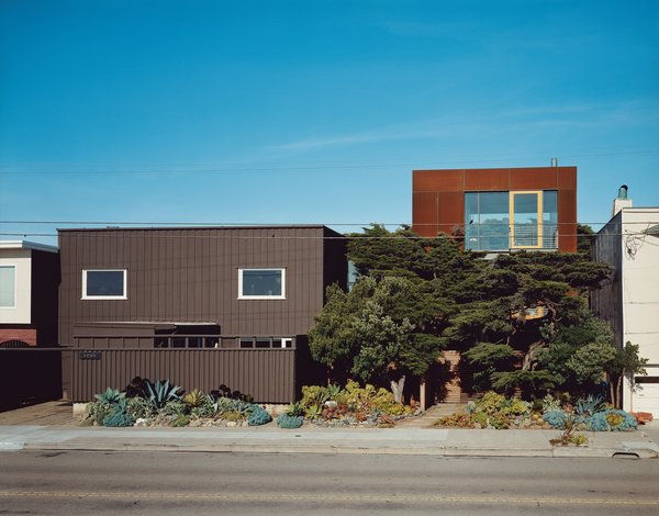 The original house (left) only gave two glimpses of the vast Pacific Ocean out of the west-facing windows—an unusual choice given the epic sweep and clear cachet of an uninterrupted ocean view. Aidlin Darling Design took a different tack with the new addition (right), using the cypress trees as a natural screen to shield the lower levels while opening the third floor to stunning views. The Cor-Ten steel cladding on the new house is designed to further redden and rust with the help of the obliging sea air.