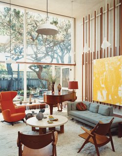 Born outfitted the living room of the original house with vertical slats on which to mount any manner of visual material. Artwork becomes easy to move around, but Lloyd-Butler likes the placement of a painting by Wayne Gonzales depicting Lee Harvey Oswald.
