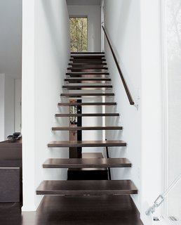 Interior wood stairs are pared with a top-floor steel staircase outside.