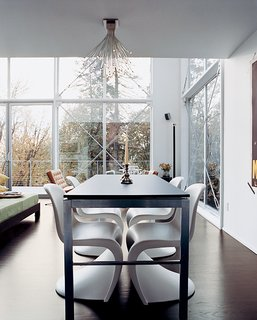 The house's open spaces are minimally furnished with modern classics like Verner Panton chairs in the dining area.