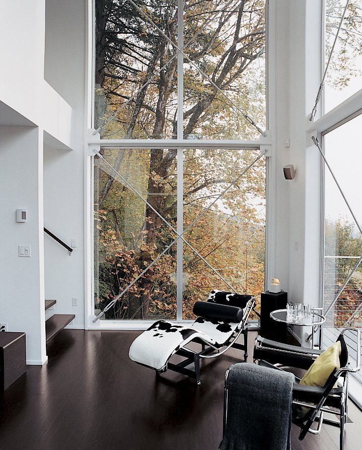A Corbusier chaise and Eileen Gray end table fill out the corner of the couple's high-ceilinged living area, which helps create the desired loftlike feel of the home. Tagged: Living Room, Recliner, and Dark Hardwood Floor.  Photo 8 of 8 in Aloft in the Forest