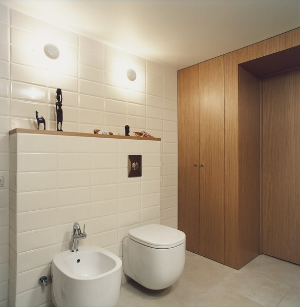 In the bathroom, which is tucked under the mezzanine, the toilet-bidet set from Pozzi Ginori boasts rounded rectangles with pleasingly deep but minimal basins. The wall sconces are from the Spanish lighting company Vibia, and fit neatly between brick-like rectangular tiles.