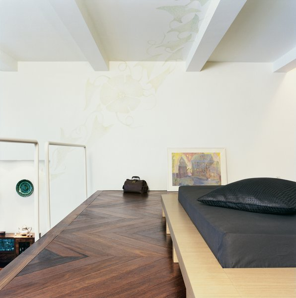 The platform bed was designed by the architect. The pattern on the ceiling was drawn by Rasa Baradinskiene, a local designer, in colored pencil over the off-white paint. Mikulionis and Marcinkeviciute don't worry about slipping through the rails to the living room level below.