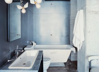 10 Ideas For the Minimalist Bathroom of Your Dreams - Photo 6 of 10 - Winged light bulbs, part of an Ingo Maurer fixture, bring levity to this bathroom. The space features a zinc wall by Houston metalworker George Sacaris, who also did the bathroom and kitchen cabinets.