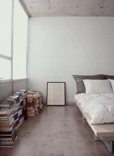 Stripped Ease - Photo 8 of 11 - Who needs shelves when there's plenty of floor space? Stacks of books and a framed print sit alongside a Peter Maly Ligne Roset bed, reupholstered in stiff linen.