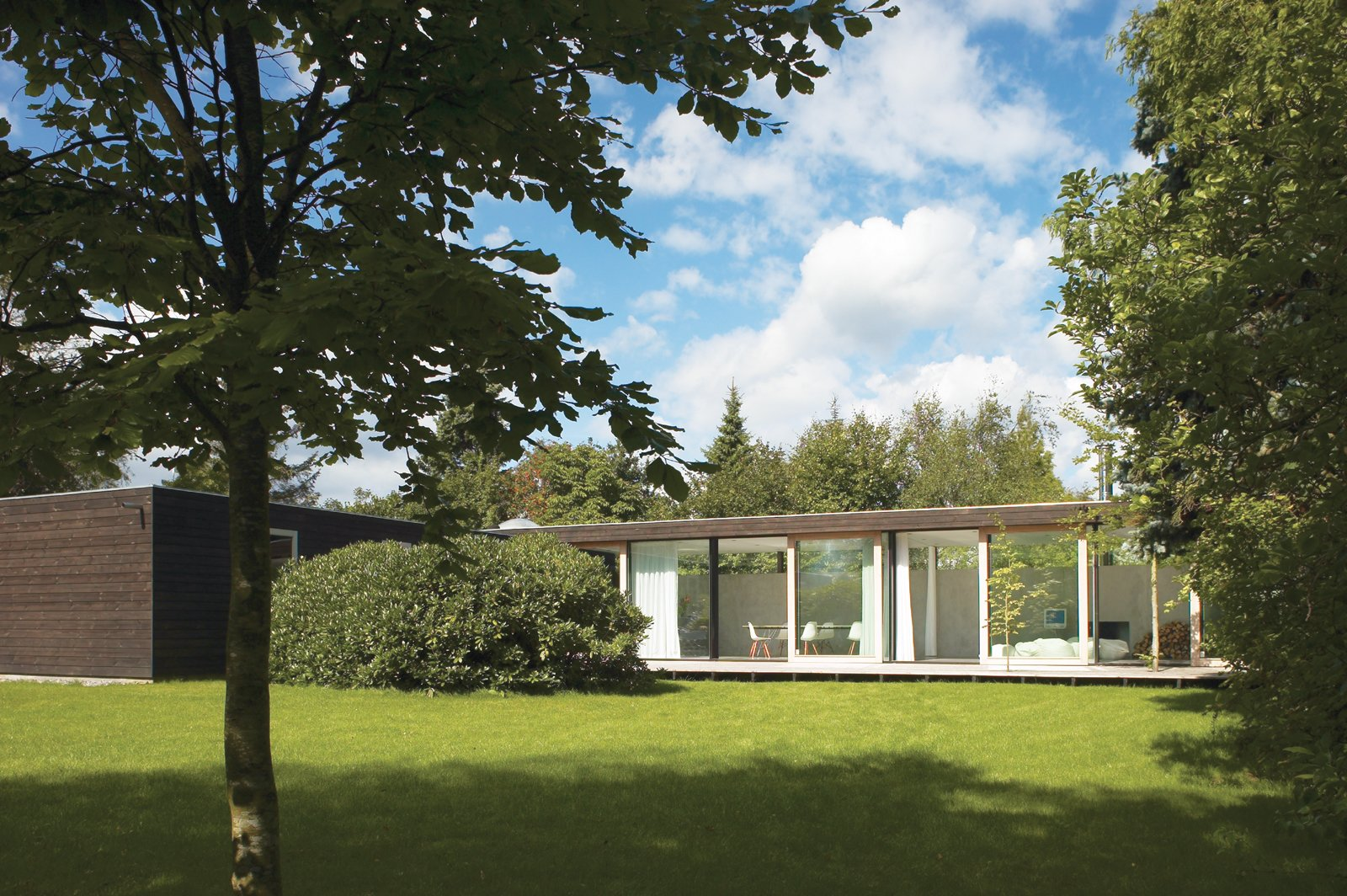 The main living space is constructed of immense I-profiles, allowing for a full wall of glass with four large sliding doors that open to the backyard. Tagged: Exterior, Mid-Century Building Type, Flat RoofLine, and House.  Photo 1 of 6 in We Summer in the Hamptons