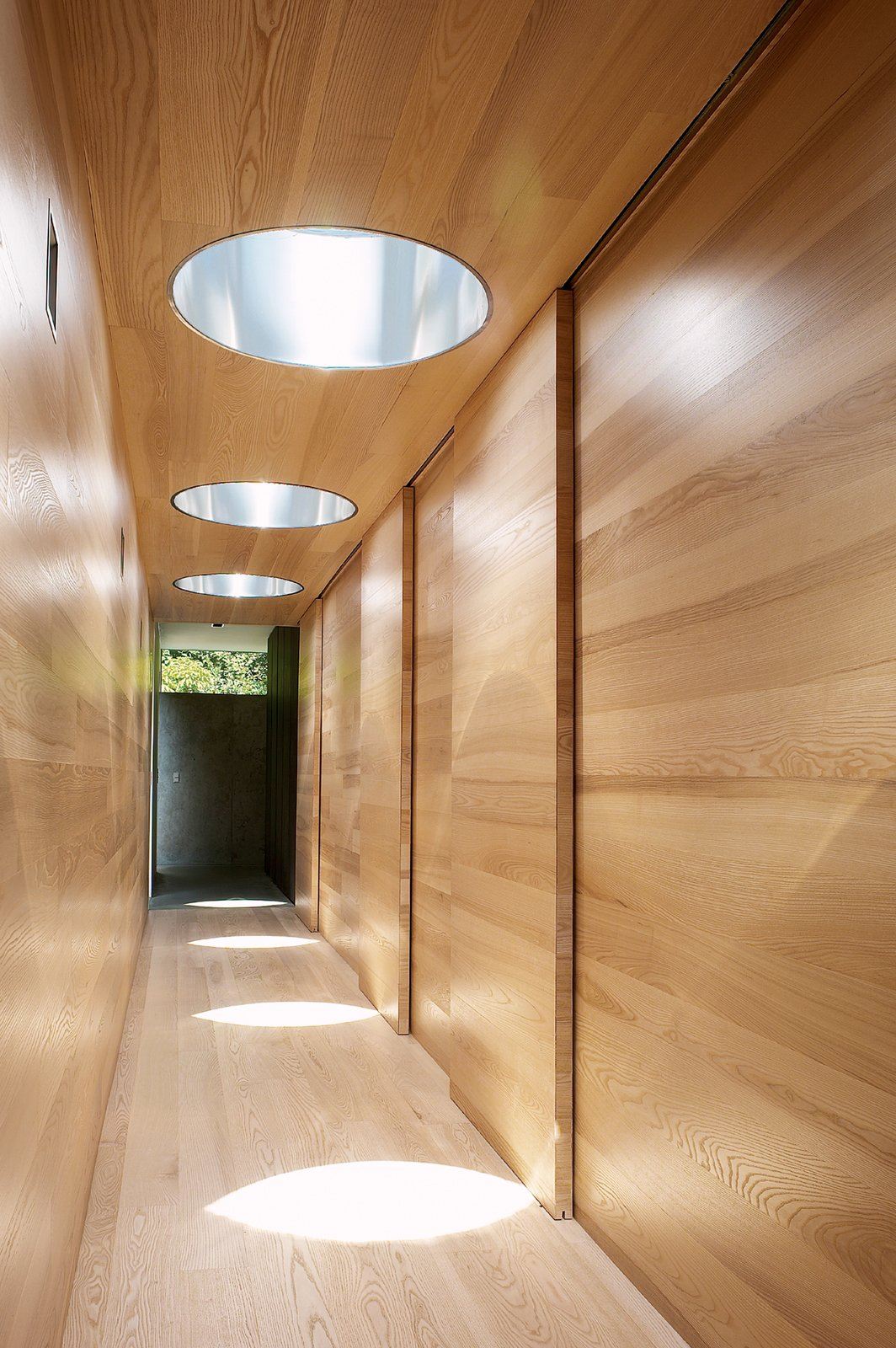 In the bedroom wing, sunlight shines down from the Plexiglass bubbles. Steel in the cutaways reflects the light. Tagged: Hallway and Light Hardwood Floor.  Photo 4 of 6 in We Summer in the Hamptons