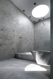This coolly modern sanctuary in Denmark echoes the elegant austerity of resident Nick Zappon's films. The master bathroom was constructed in concrete with a circular bathtub and accompanied by a parallel circular cutaway in the roof that allows contemplative bathers to view the stars from the tub.