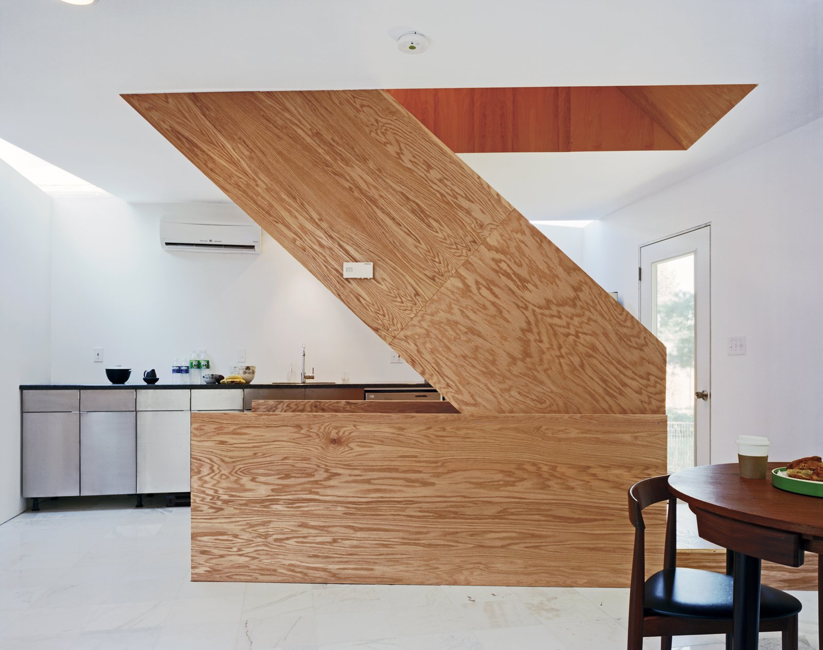 The wooden stairwell in the center of X-Small provides a pivot point from which the rest of the house rotates. The floor is Carrara marble bought from Olympia Marble and Home Depot.  Photo 1 of 11 in Four Houses and a Future