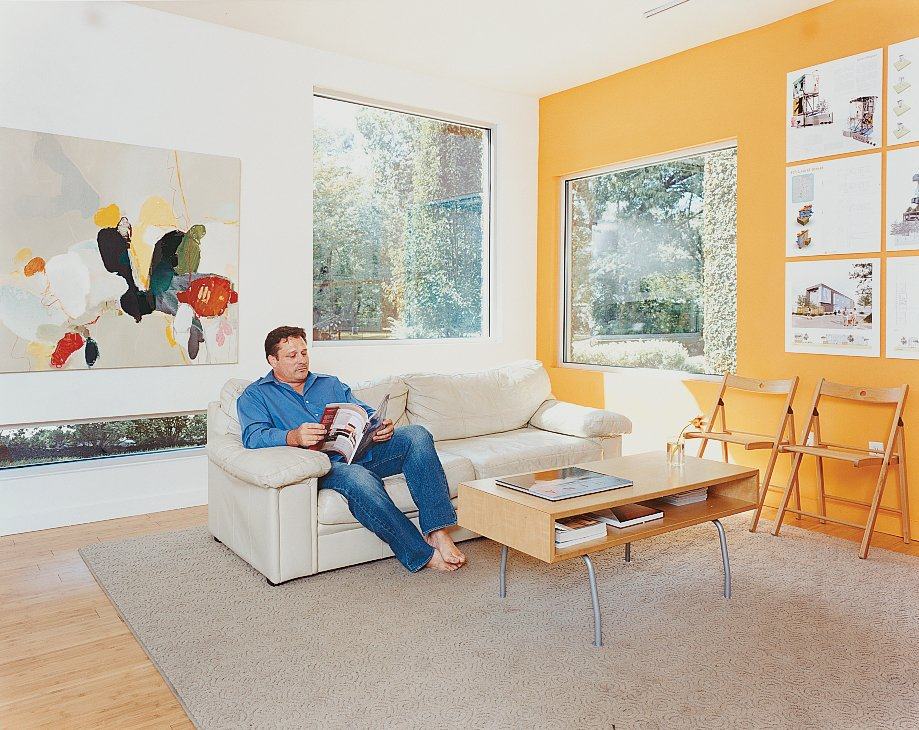 Baird relaxes in the bright living room, which is decorated spartanly with the architect's own artwork, a couch, and a coffee table by IKEA. Baton Rouge Oasis - Photo 4 of 13