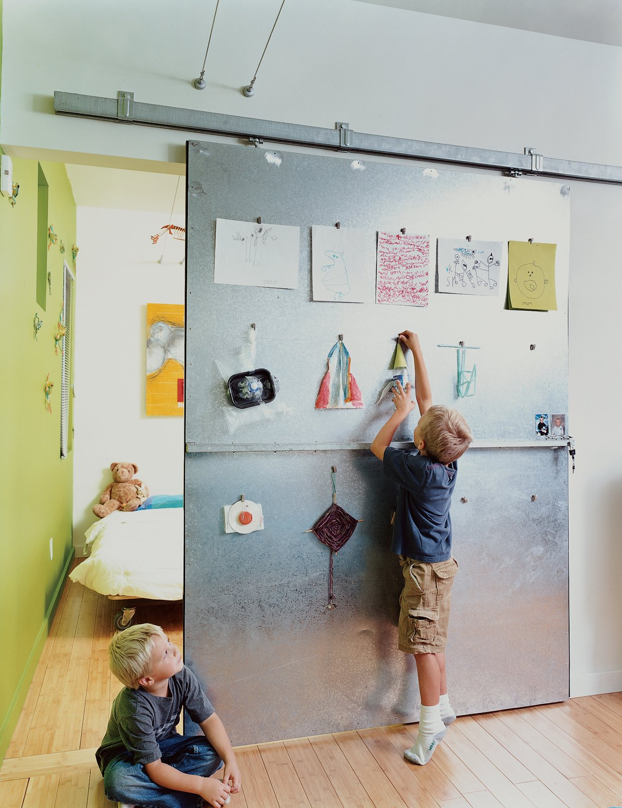 David Baird designed the custom sliding doors with materials and hardware from Home Depot. The doors also act as a makeshift critique wall for Bo and Sky's artwork.