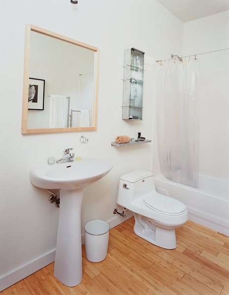 The family opted for modest—and cheap—design choices in the kitchen and bathroom (above), which are commonly the most money-sucking rooms in a home.