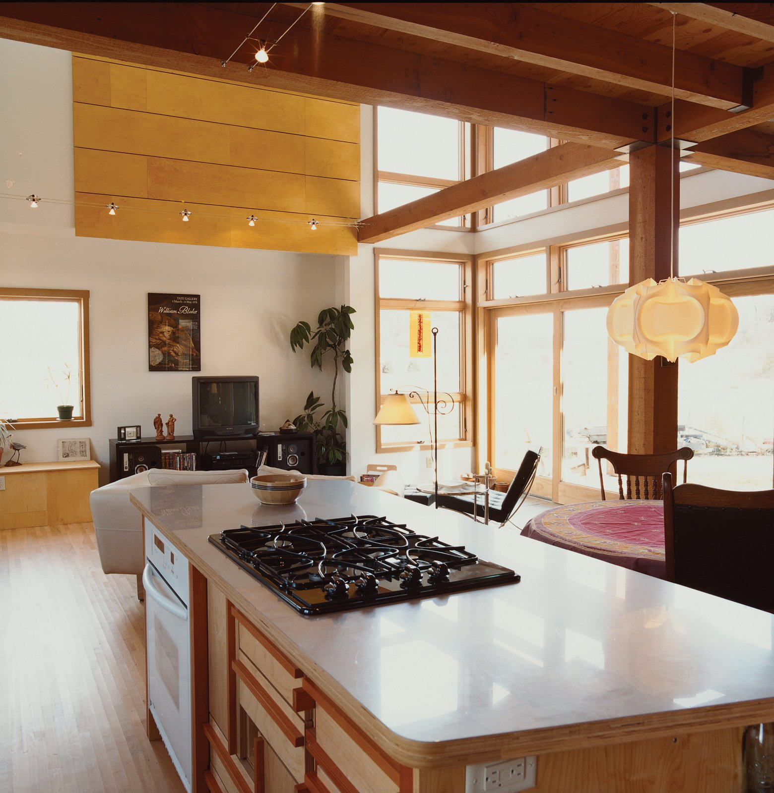Light pours into the combined living, dining, and kitchen space at the front of the house. Antique furnishings are offset by the striking Pendant 169 lamp by Danish architect Poul Christiansen for Le Klint.  Photo 4 of 12 in Labor of Loved Ones