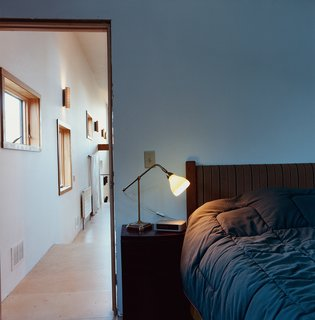 A hallway lined with windows provides a distinctive gateway to the bedroom.