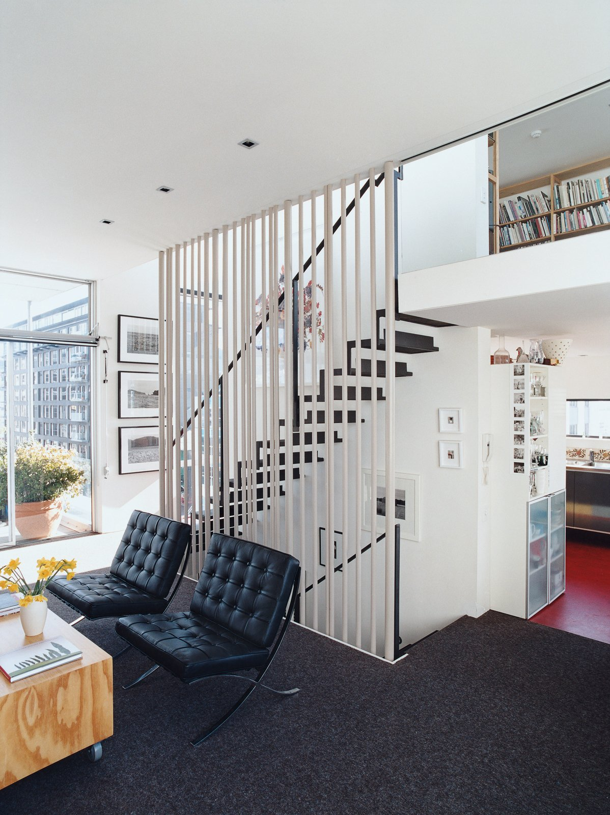 A floating steel staircase ties the living area and loft together. Variegated steel tubes provide graphic punch while maintaining the apartment's airy and open feeling. Tagged: Living Room and Chair.  Clever Loft Spaces for Small Places by Diana Budds from Rising Above It All