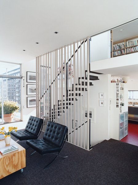 A floating steel staircase ties the living area and loft together. Variegated steel tubes provide graphic punch while maintaining the apartment's airy and open feeling.
