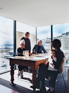 Rising Above It All - Photo 5 of 10 - Jan Bieringa (seated, left) hangs out with her son, Kris Bieringa (standing), Tony Hiles, Judith Fyfe, and Fyfe's granddaughter, Phoebe Pottinger. Surrounded on three sides by glass walls, the dining room is the perfect spot to soak up the stunning views <br><br>of Wellington Harbor and the hilly eastern suburbs.