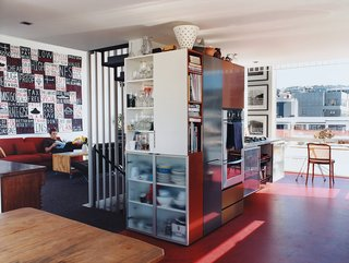 Rising Above It All - Photo 8 of 10 - A densely packed built-in unit divides the kitchen area from the living room, and provides streamlined storage for appliances and kitchenware. The Bieringas are avid collectors of New Zealand art; the painting to the left is by Peter Robinson, and the many photographs peppering the apartment are by important Kiwi artists Luit has championed over the years.