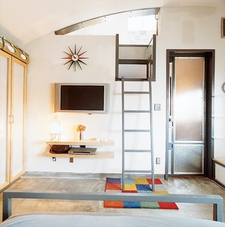 A ladder leads up to the bedroom, which is tucked under the curve of the vaulted roof. The Sunburst clock is by George Nelson; the flat-screen TV is by Philips.