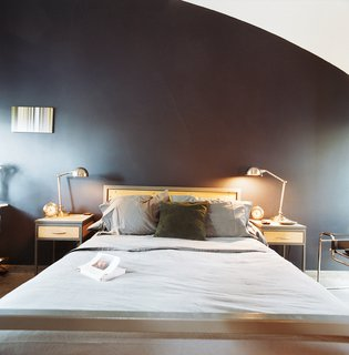 """The architects designed the bed and nightstands themselves and picked up the lamps from Target. """"We've found that you can mix design and commodity stuff well if you're attentive to the overall presentation,"""" says Schatz."""