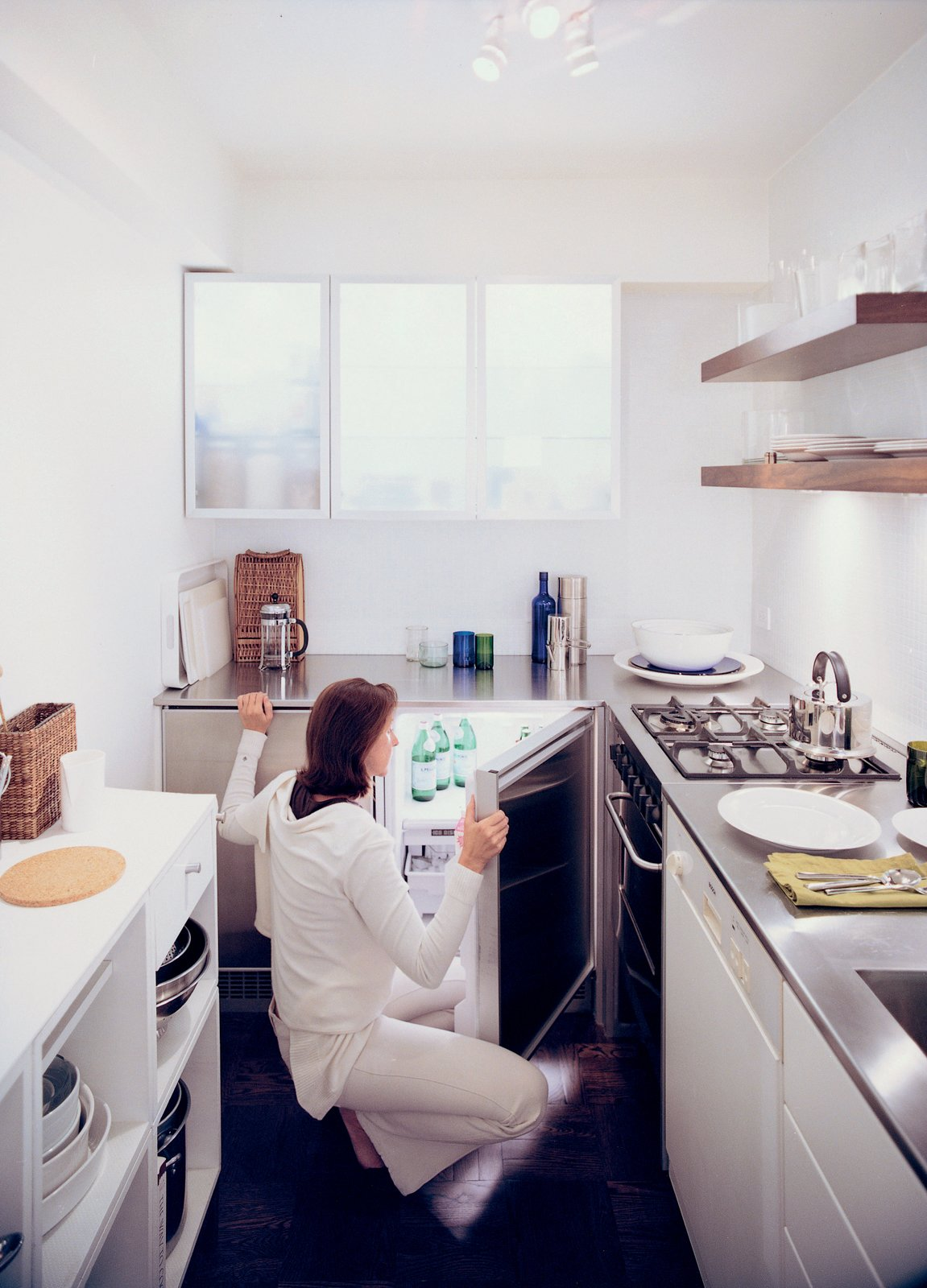 Goolrick reoriented the kitchen and chose sleek stainless steel countertops and bright white walls and cupboards to create the illusion of space.