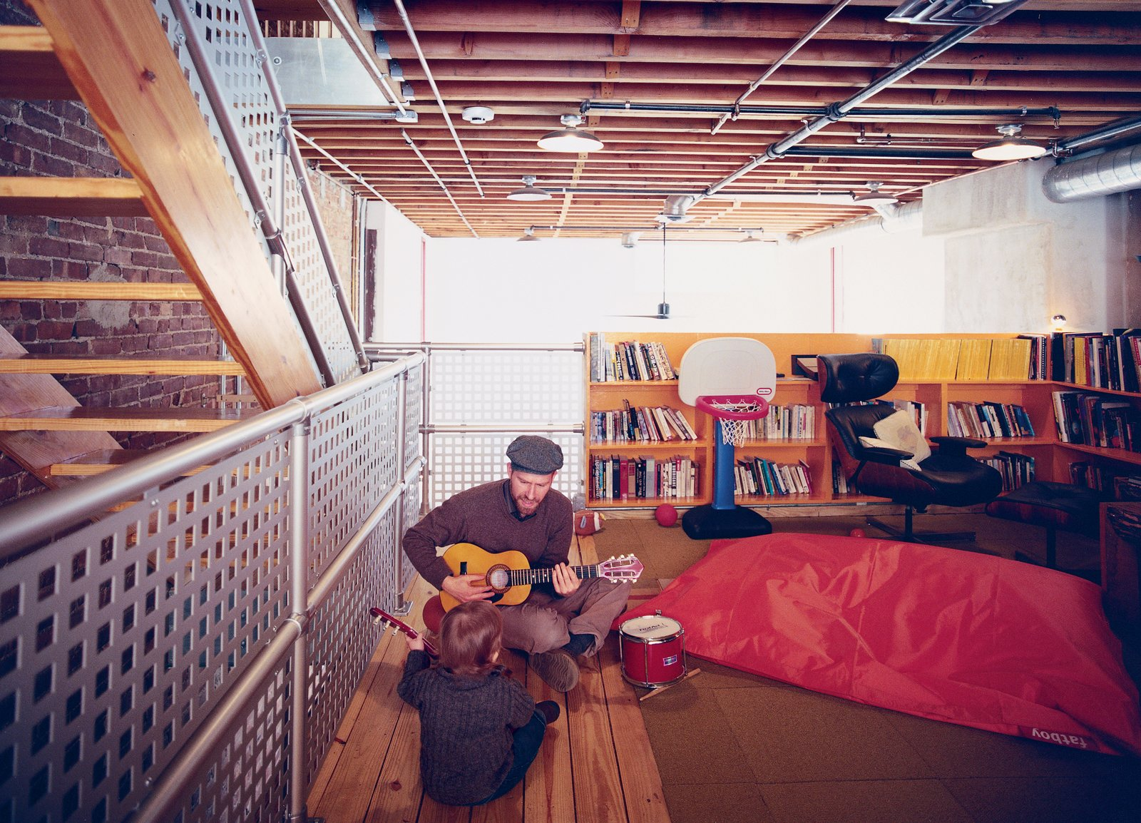 In the family room, Lucien gets an early start on his music career with his father's help. The space, technically the third floor of the structure, overlooks the central living area below. Tagged: Kids Room, Playroom, Medium Hardwood Floor, and Shelves.  Photo 5 of 5 in A House Grows in Brooklyn