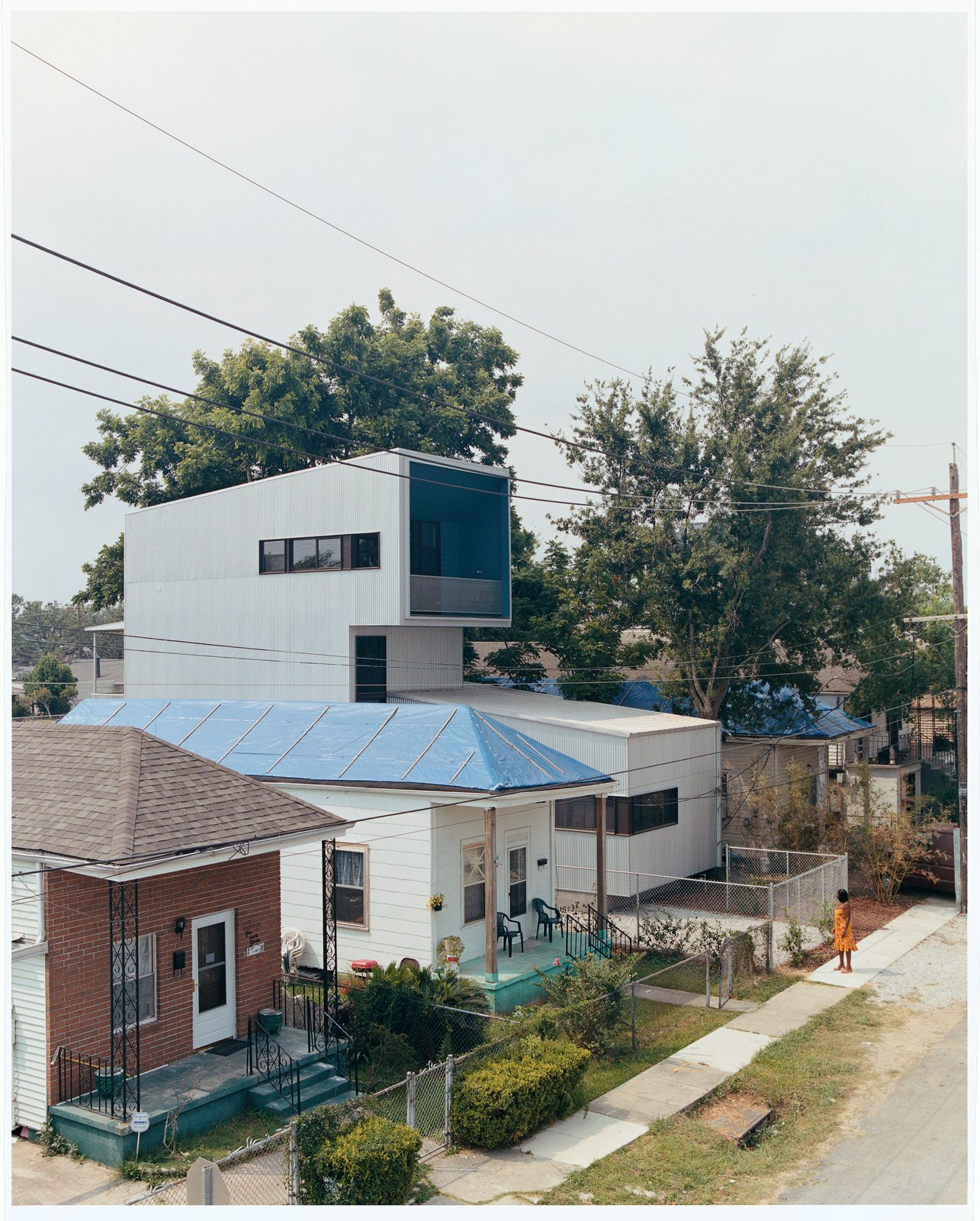 Bild Design introduced the new structure seamlessly with the help of builders A.J. Christiana Construction. Ms. Doris, whose tarp-clad house to the left lost much of its roof when Hurricane Katrina struck, checks out her new neighbor.  Photo 1 of 11 in New Orleans, LA