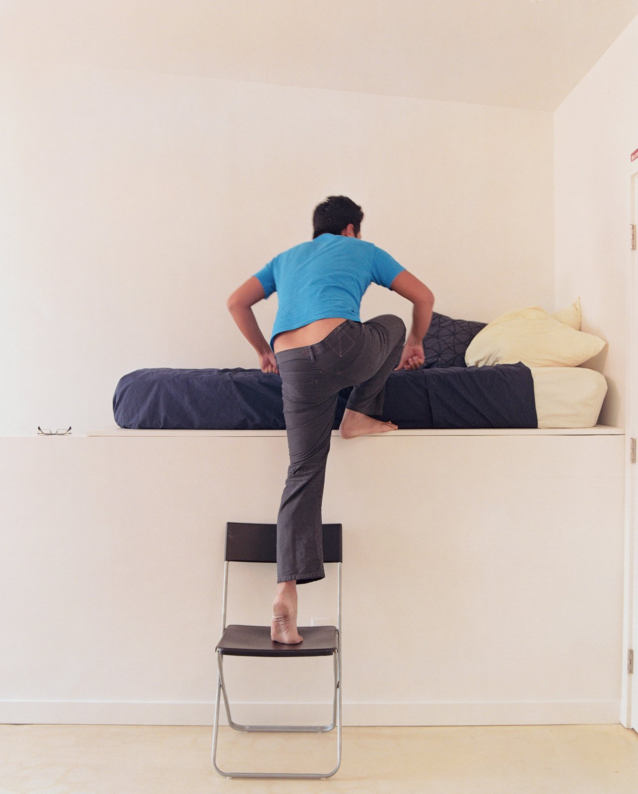 Jeremy Claud ascends to his bed, which is on a raised platform that hovers over a staircase.