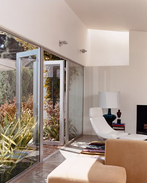 Seven-foot-high glass doors bring the garden, landscaped by Jay Griffith, into the living room. A skylight brings even more light into the white-walled room with polished-concrete floors. There is a splash of color in a custom rug designed by Dawn Farmer and made by Della Robbia, which also made the sofas.