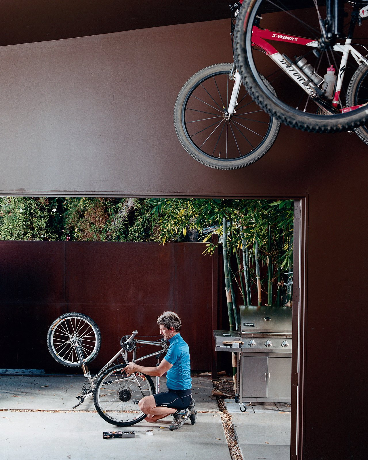 Pierre Kozely mends his bike on a patio in the rear yard, seen from their garage—which was transformed into a media room. Behind him is a Cor-Ten rolling gate that gives access   to the back alley. Venetian Vicissitude - Photo 7 of 9