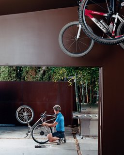 Pierre Kozely mends his bike on a patio in the rear yard, seen from their garage—which was transformed into a media room. Behind him is a Cor-Ten rolling gate that gives access <br><br>to the back alley.