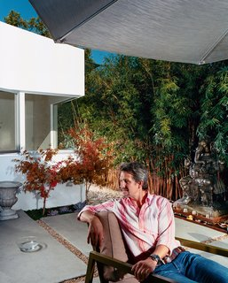 The front, middle, and rear yards are conceived as outdoor rooms. Pierre Kozely relaxes <br><br>in the middle yard in a prototype of an outdoor furniture line by Pietrarte. A bronze Ganesh is on a raised pedestal in the middle of a small water feature.