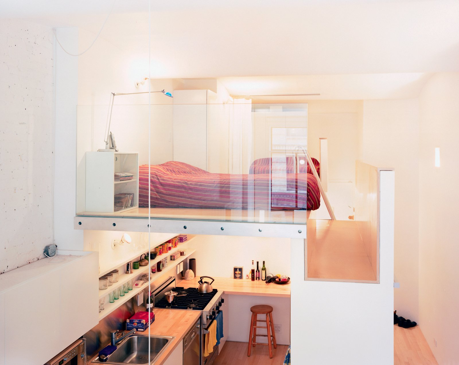 "The volume that both incorporates the single closet (accessible from the hallway) and the refrigerator (which opens into the kitchen) and serves as the bedroom floor is, says Kyu Sung Woo, ""where everything comes together.""  Photo 2 of 7 in Big City, Little Loft"