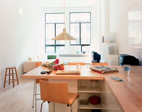 "The combination dining table/countertop, says Woo, ""is both a demarcation and connection between the kitchen and main living space."" Originally, the architect considered a concrete surface, but balked at the delivery time and expense. ""I kind of like it as it is built,"" he says. ""All the horizontal surfaces are wood."" The Conical pendant lamp is by Jorgen Gammelgaard and the Compasso d'Oro bar stools are by Enrico Franzolini."