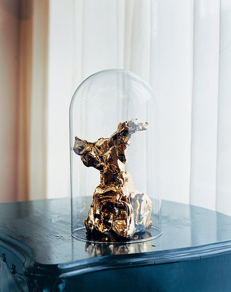 A gold-plated One Minute sculpture, under an antique glass dome.