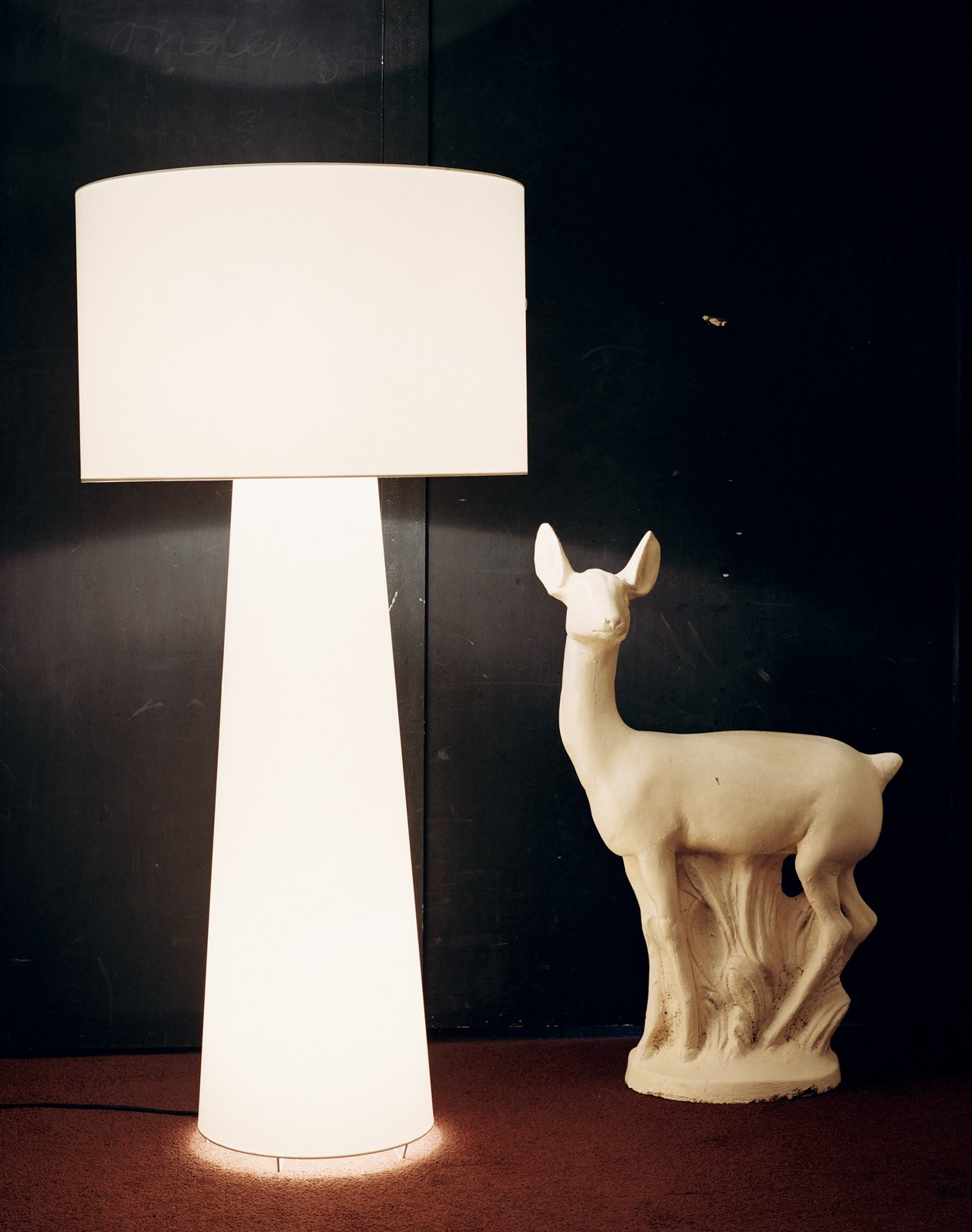 A luminous Big Shadow in white casts an ambient glow against a wall coated with blackboard paint and a chocolate brown carpet. The origin of the plaster deer figure has been forgotten. It was acquired as a possible inspiration source and has moved around the designer's studio and home ever since.  Photo 8 of 11 in Marcel Wanders