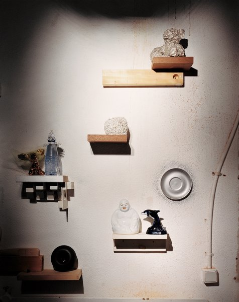 An installation of mismatched handmade shelves makes a display area for another enigmatic assortment of objects, including a Wanders Sponge vase (1997), made by soaking a real sponge in clay, which burns away when the piece is fired. The same technique was used on the silver-plated teddy bear above it. The dolphin and Buddha figures—perhaps a reminder of Wanders's role in mainstreaming kitsch—illustrate the designer's interest in ordinary, popular decorative objects.