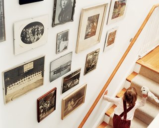 "Row House Revival - Photo 7 of 8 - ""You have all this history underneath you here,"" says Matthew Bardin. A display of evocative old family photos, arranged in the stairwell, underscores Bardin's point."