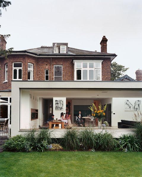"Architect Gregory Phillips connected the original house to a new modern extension that doesn't interfere with the surrounding houses. ""I try to be true to the location,""he explains, ""so it doesn't seem like some spaceship has landed."""
