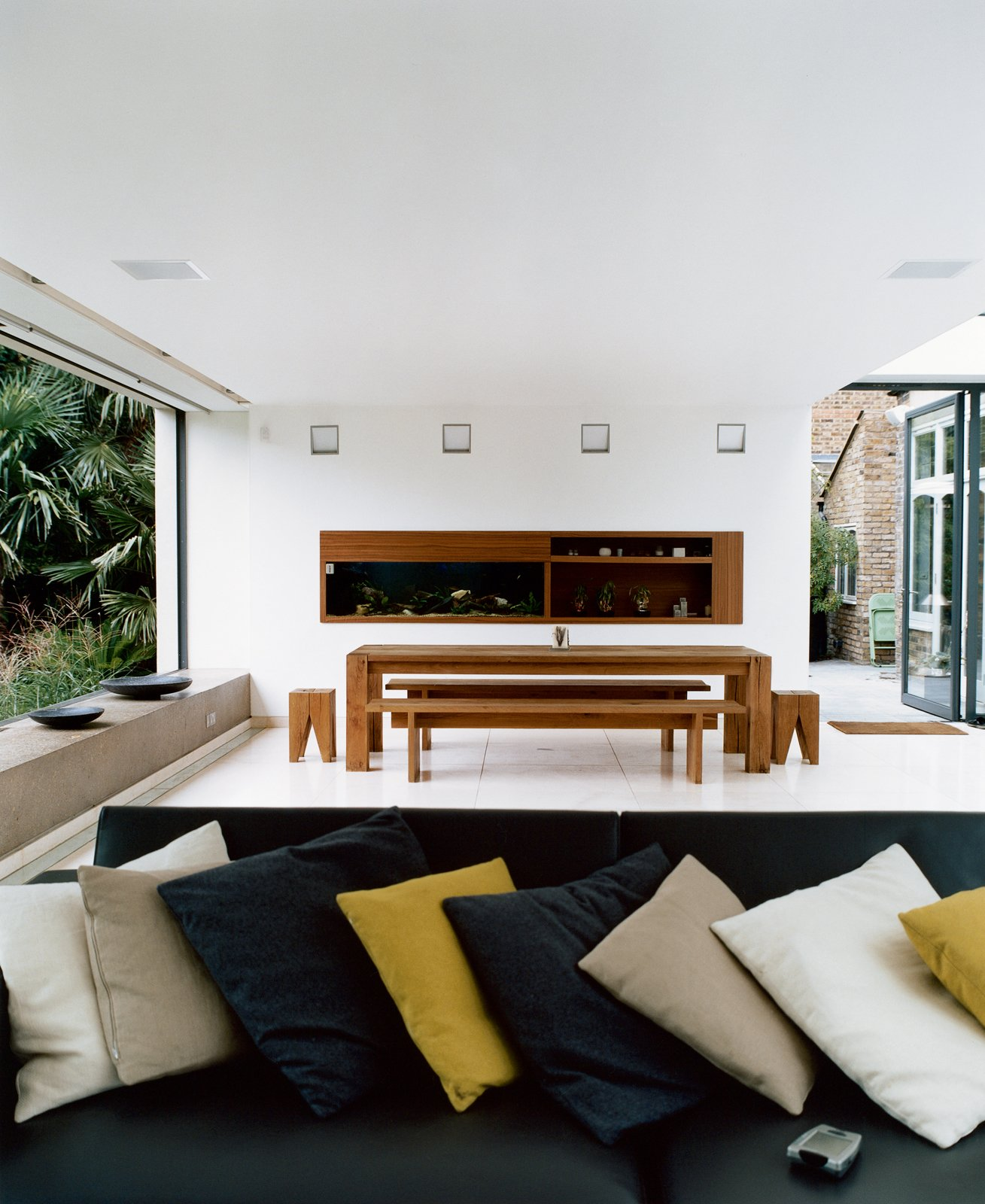 The new space was conceived as a blank canvas so that the decidedly nontraditional English garden—a large lawn bordered by exotic palms, bamboos, ferns, and other flamboyant foliage inspired by a recent holiday to Australia—could be the focal point. The minimalist dining table, benches, and stools are by e15.