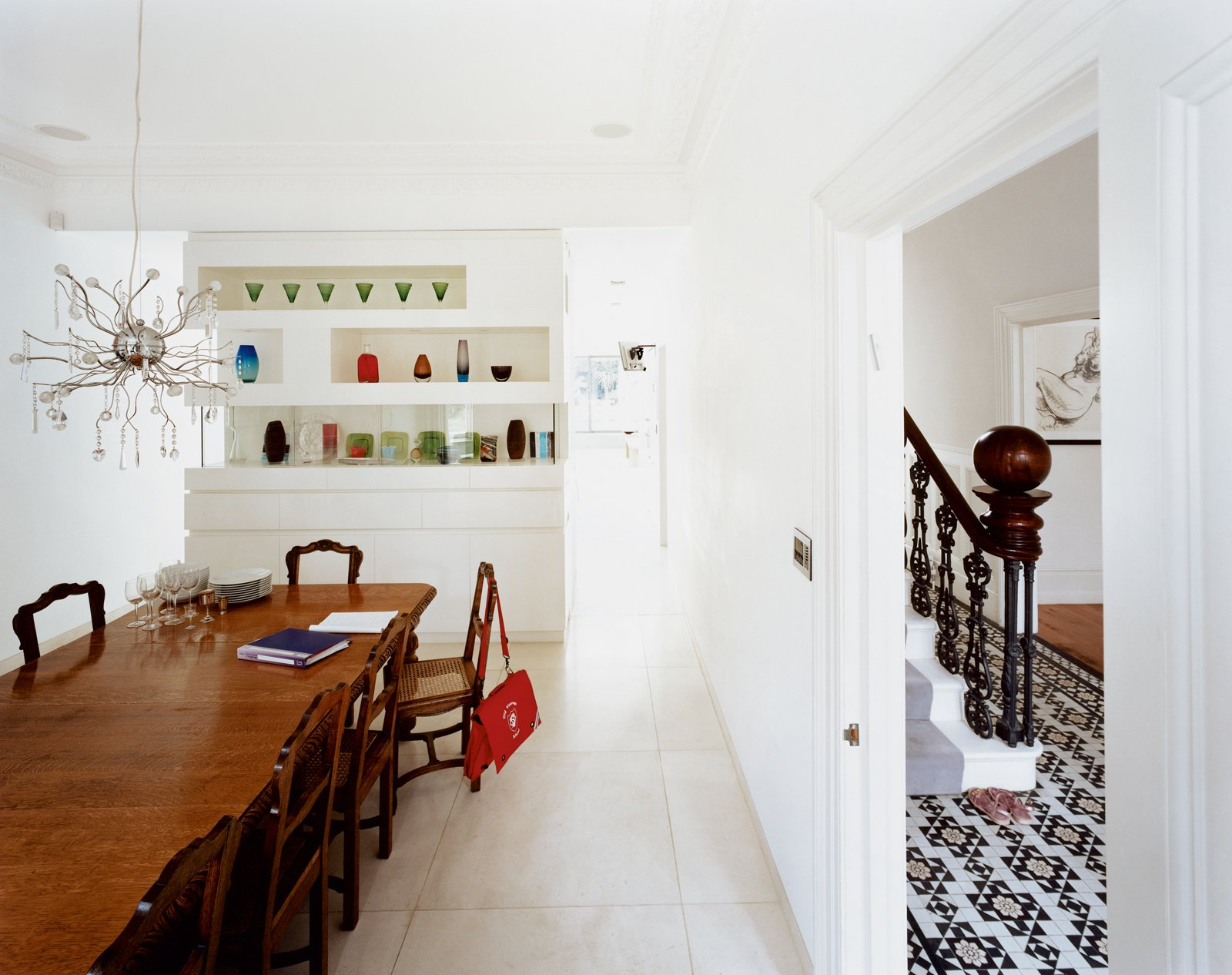 """""""I like the idea of houses having layers,"""" says Phillips, who incorporated the home's strong traditional features into his design. He kept the formal dining room, for example, which is divided from the kitchen by an elegant cabinet displaying colorful glass vases, but also created a more casual dining environment in the new extension.  Photo 7 of 10 in Victorian Secrets"""