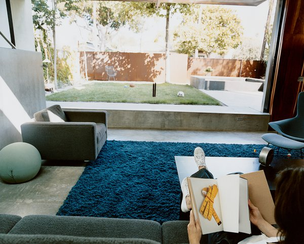 The living room flows effortlessly out to the courtyard. This unity is underscored by the living room's blue shag rug from the Shag Rug Company.