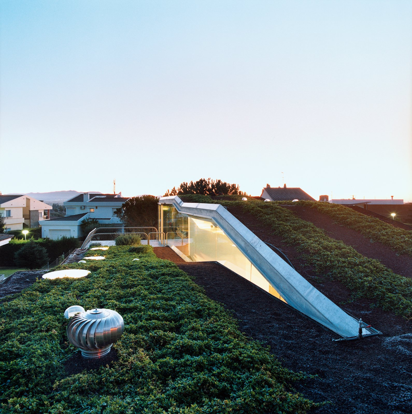 The hydroponic rooftop garden grows out of volcanic stones. The home is conceived as a giant C-shaped spiral. Tagged: Outdoor, Rooftop, Grass, and Gardens.  Photo 3 of 11 in 10 Modern Rooftops For Summer Relaxing and Entertaining from Suburban House of the Future by Cloud9